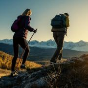 Two hikers climbing a ridge at sunset