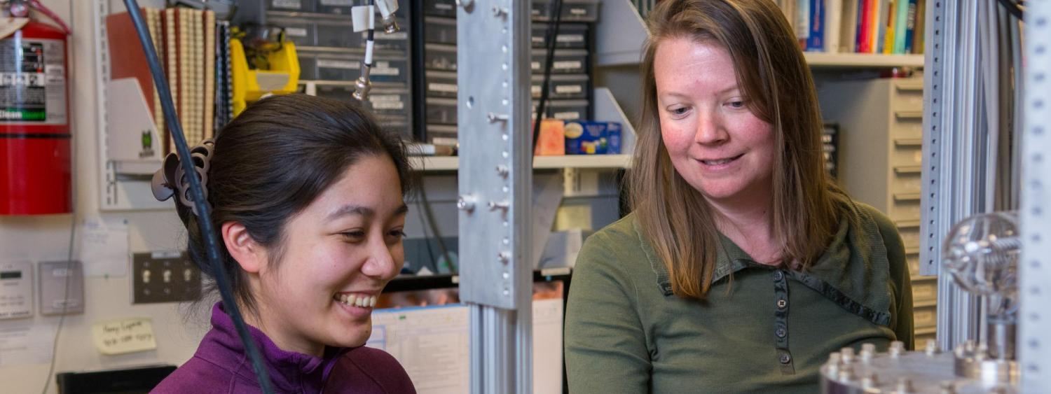 Two women work on a physics instrument