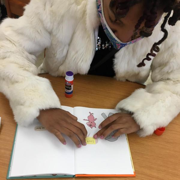 Girl adding braille to an Elephant and Piggie book.