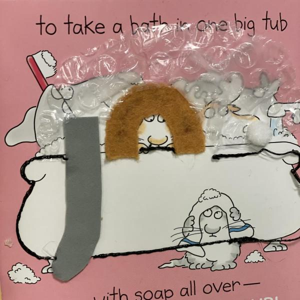 Tactile page with textures for an elephant, lion, and rabbit taking a bubble bath
