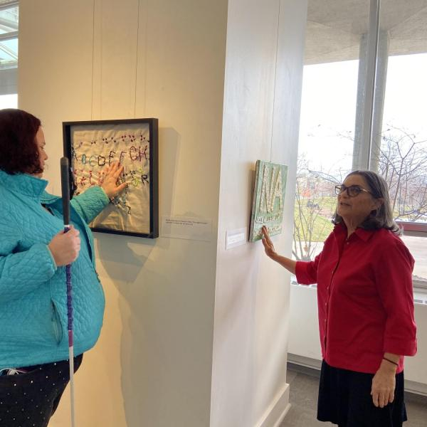 Artists Jenni Holcomb and Ann Cunningham with Jenni's embroidered sampler.