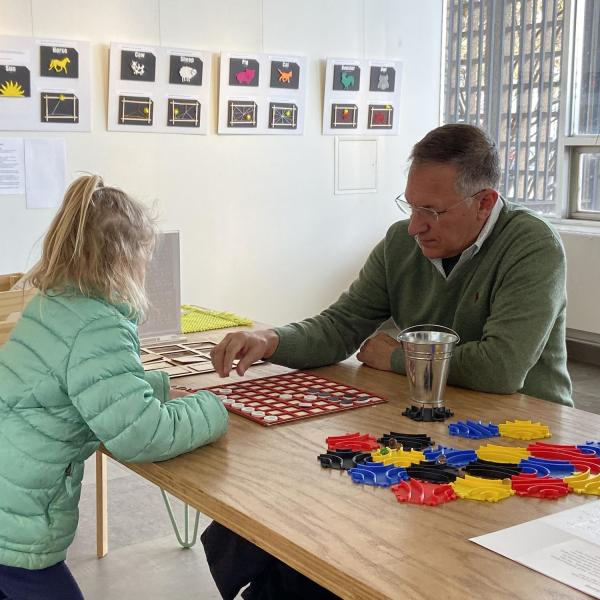 Girl and grandfather playing tactile version of Othello.