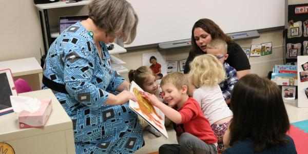 Librarian sharing tactile boardbook with preschool students