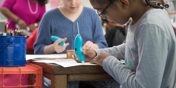 Girl at desk using 3D pen.