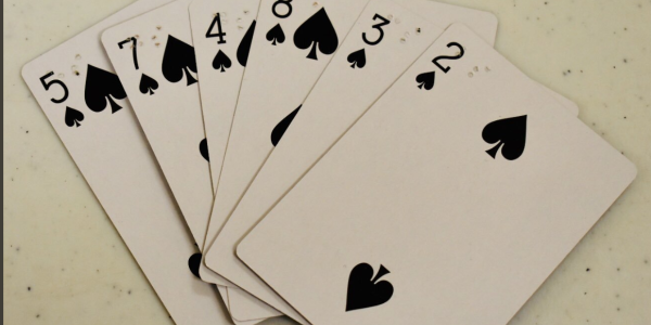 Six playing cards showing different numbers in spades with braille.