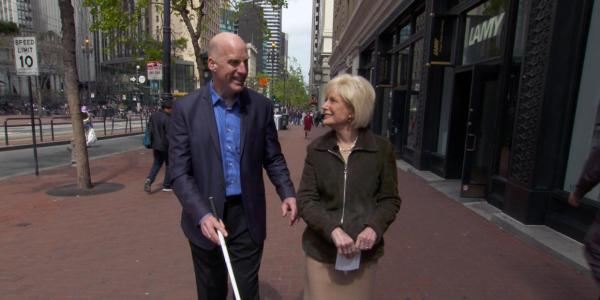 Chris Downey walking along the street with correspondent Lesley Stahl.