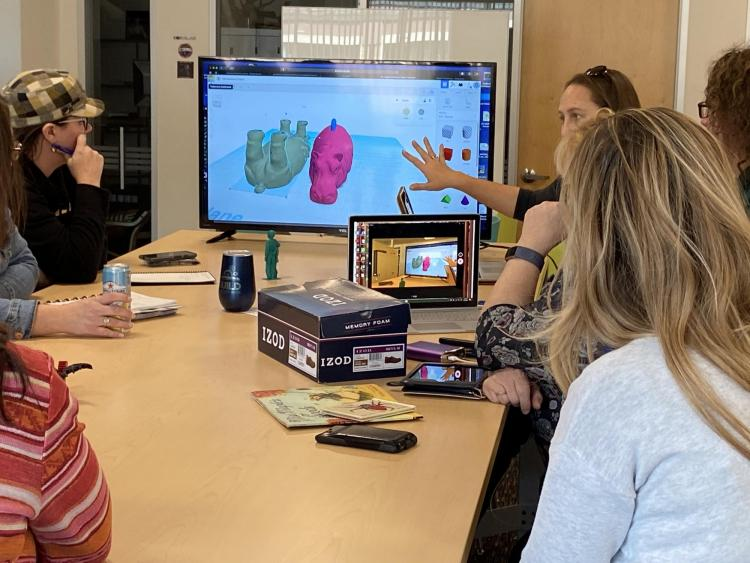 Group of people sitting around table viewing computer screen with TinkerCAD design.
