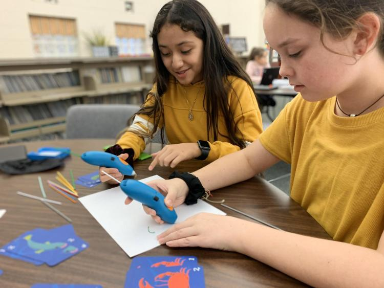 Two students working with 3D printing pens