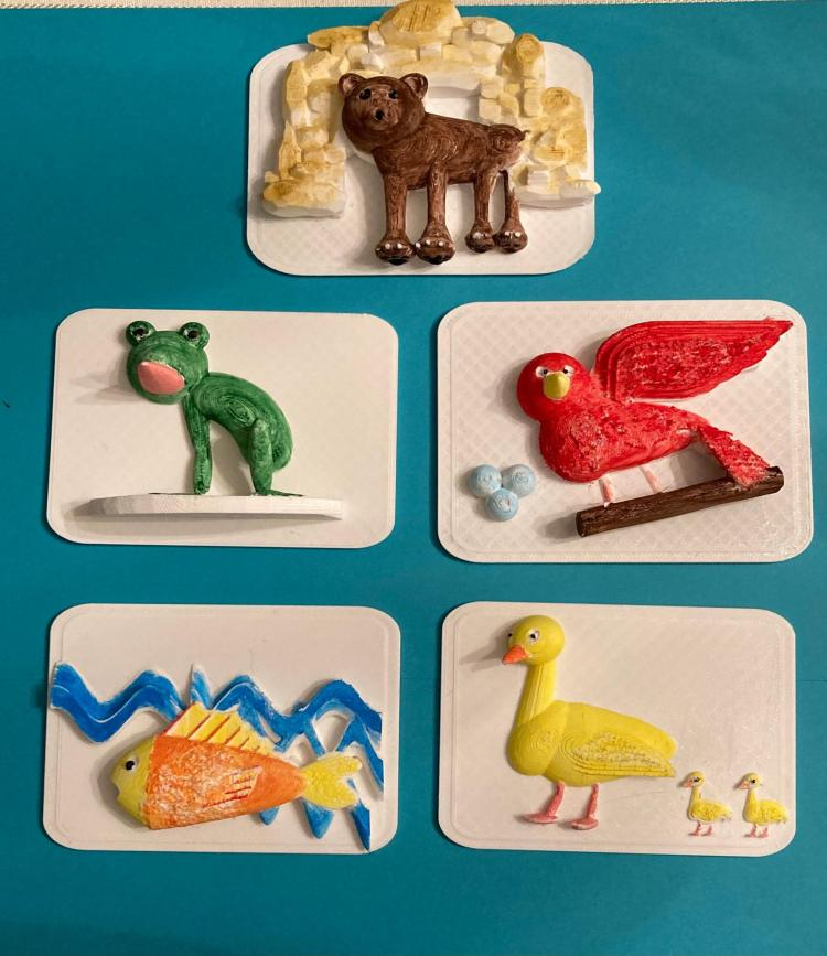 Five 3D printed pages that have been painted, showing different animals from the book