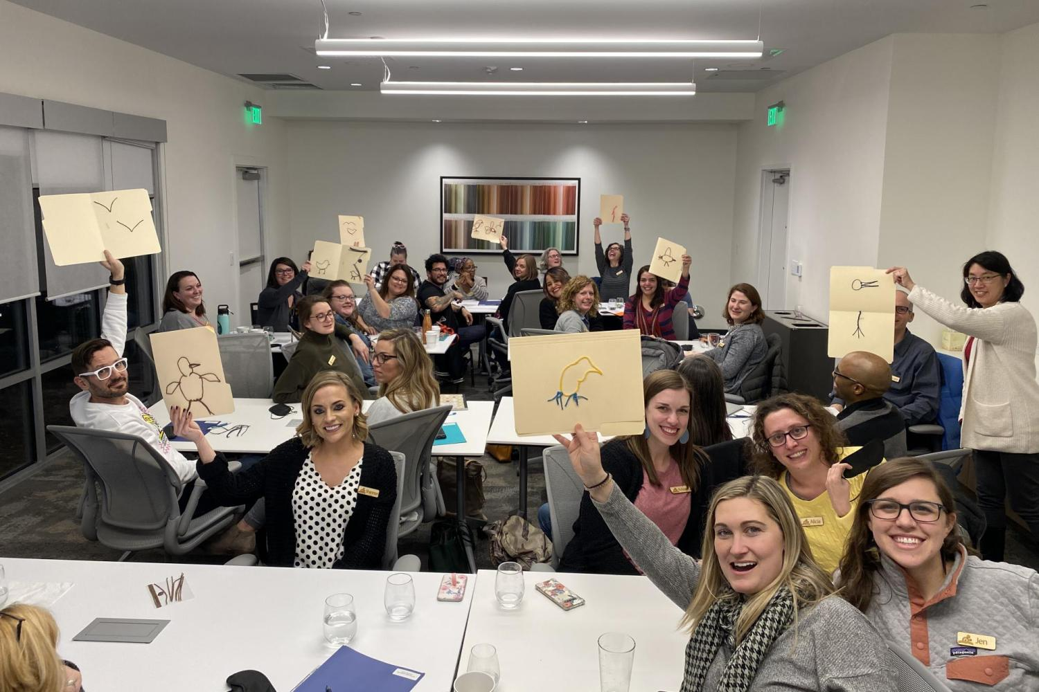 Group of people holding up tactile pictures of birds