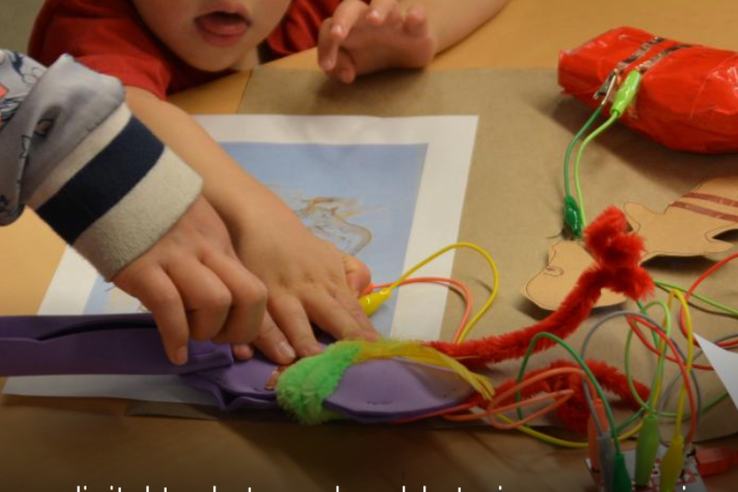 Children's hands working on a crafted page with construction paper, pipecleaners, and make makey board
