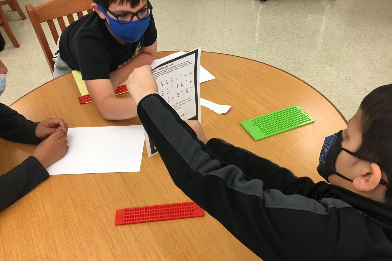 Two boys working with braillers and consulting a braille chart.