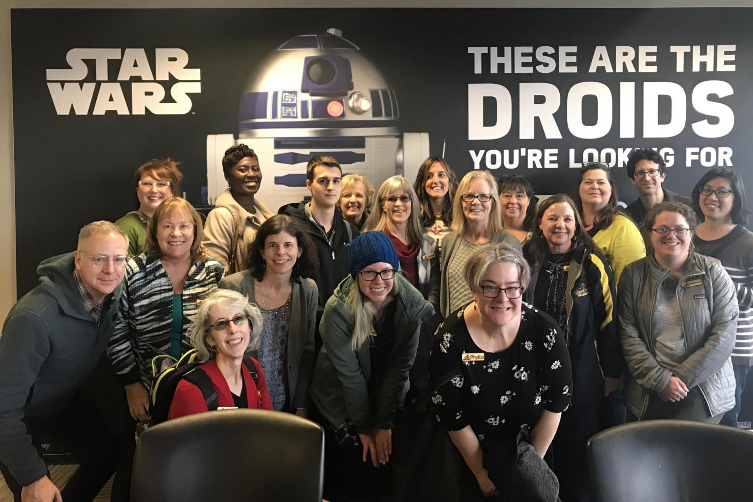 Workshop attendees posing in front of a Star Wars poster