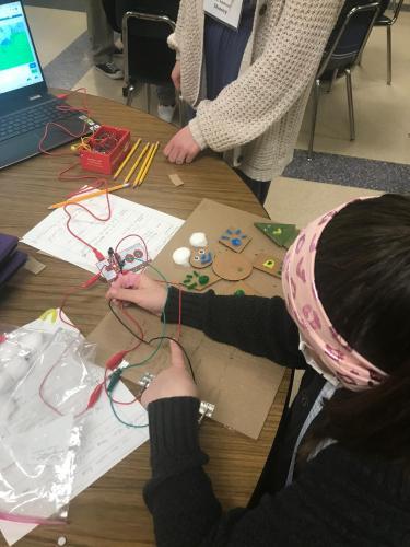 Girl adding sound to tactile cardboard drawing using a Makey Makey kit.