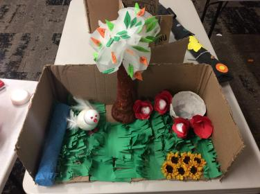 Box with tactile scene with handcrafted bird, tree, flowers, and grass