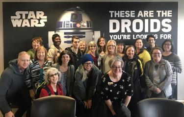 Attendees for Professional Development posing in front of a Star Wars poster.