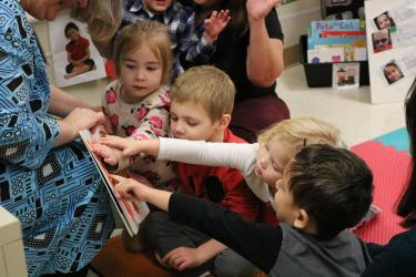 Preschool students feeling tactile lines on a board book