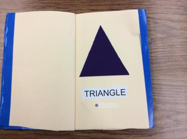 Page showing a large felt triangle with braille and English label.