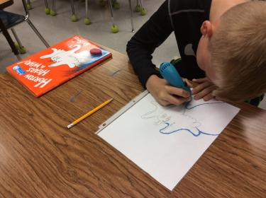 Boy using a 3D pen to outline an illustration of an elephant.