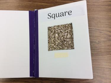 Page showing a glitter covered square with braille and English label.