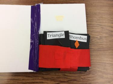 Page with pocket containing large cards with shapes on them for matching game.
