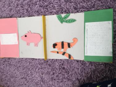 book pages with cardboard texture and braille showing pig and chameleon