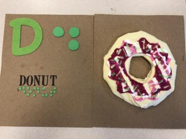 Book page for the letter D showing a puffy fabric donut with hard plastic sprinkles on top.