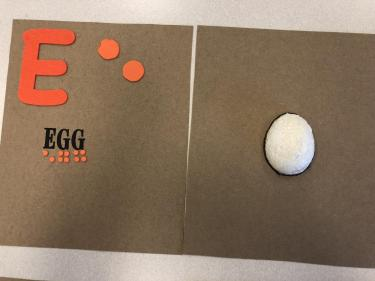 Book page for the letter E showing half of an egg made from white painted styrofoam.