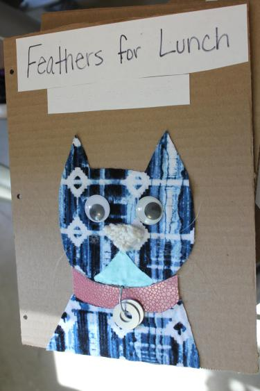 Fabric cat outline with google eyes and collar with washers as tags.