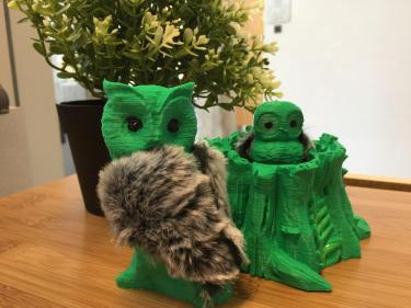 3D printouts of a mother owl, baby owl, and tree stump.