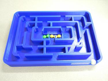 3D printed maze with raised walls and a marble for following the paths.