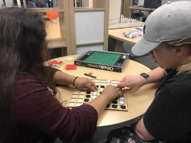 Two girls sit and play a tactile version of Othello.