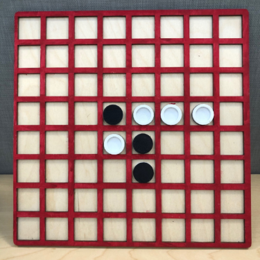 Tactile gameboard for Othello showing red grid on light background and black and white playing pieces.