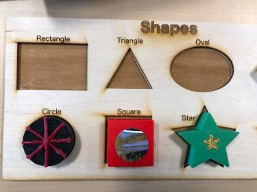 Laser cut board with outlines of different shapes and 3D modeled shapes that fit in the outline.