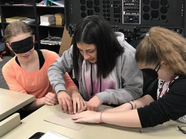 Girls with blindfolds play tactile Pictionary game.