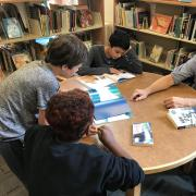 Group of teen boys with teacher reviewing picture books in library