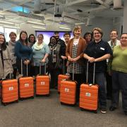 Participants in the workshop posing for a group picture with orange suitcases.