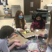 Three girls working on tactile poems with geometric cardboard shapes.