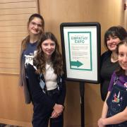 Three students and librarian posing with sign for Empathy Expo.