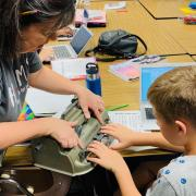 Teacher showing student how to use a Perkins Brailler.