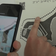 Hand pointing to parts of tactile map while using tactile images phone app