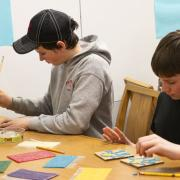Two boys working on creating tactile memory game pieces.