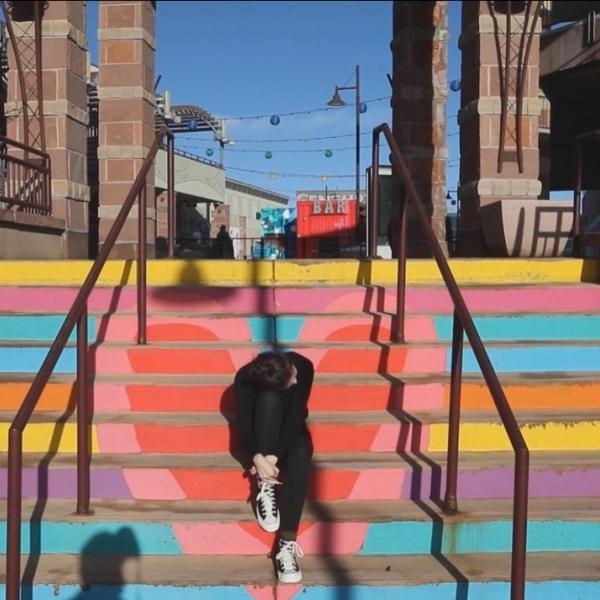 Person sitting on brightly colored steps with knee to head