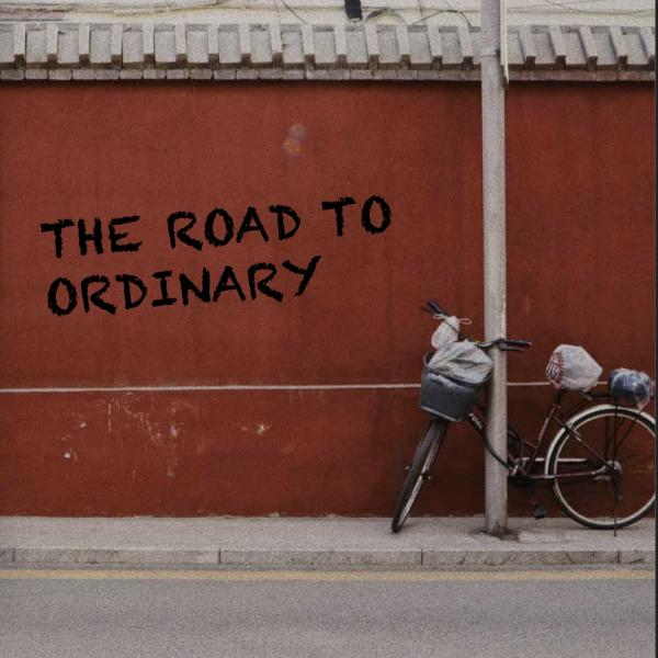 """Bicycle on the street with text """"the road to ordinary"""" on a red wall"""