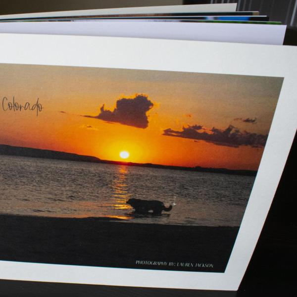 Photo book with a sunset at sea is propped on a table