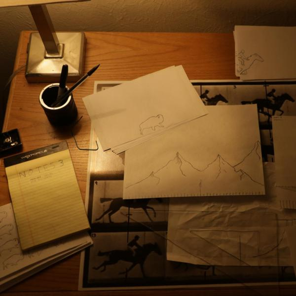 Pieces of paper on a desk with hand drawn animations