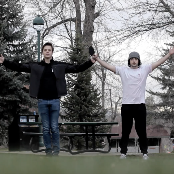 Two men on the grass holding hands in the air
