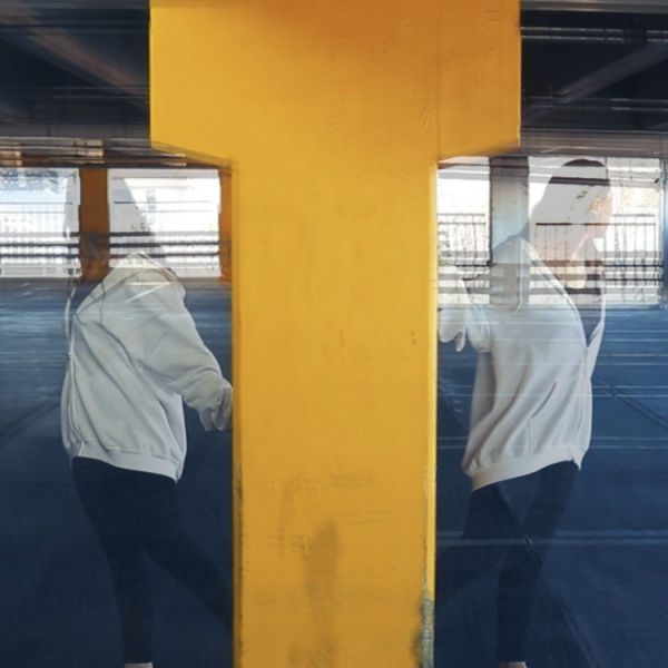Mirrored image of person in a carpark beside a yellow structure