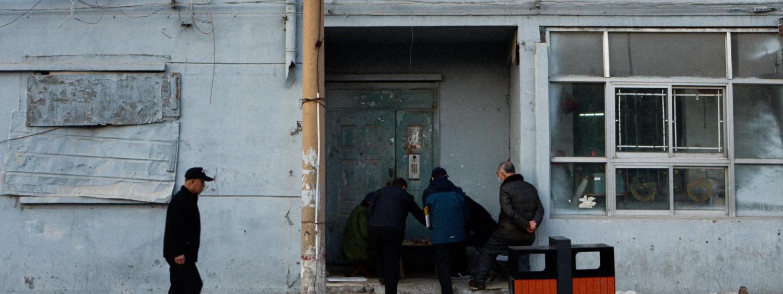 Photographic art of men by door of abandoned stores