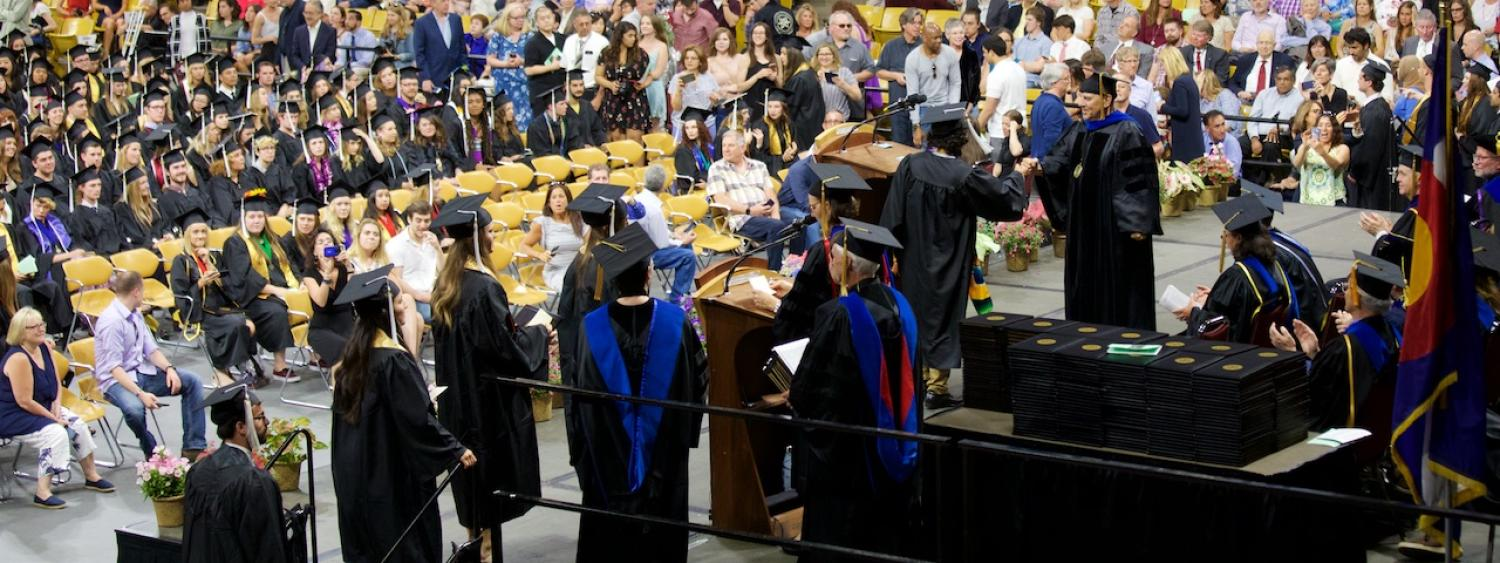 May 2018 graduates crossing the stage to be congratulated by the chair